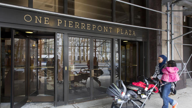 FILE- In this April 3, 2015 file photo, a woman enters One Pierrepont Plaza in the Brooklyn borough of New York. The 19-story office building rises unassumingly from downtown Brooklyn, its upper floors offering generous views of the nearby Manhattan skyline and the East River's famed bridges. Inside, the headquarters of what will arguably be the most scrutinized presidential campaign in history, Hillary Clinton's second bid at the White House. (AP Photo/Mark Lennihan, File)