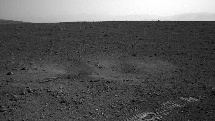 This image dated Wednesday Aug. 22, 2012 and provided by NASA shows the Curiosity rover's wheel tracks on the surface of Mars an image sent from one of the rover's cameras. The image was posted on a Tweet by JPL mission engineer Allen Chen.   (AP Photo/NASA)