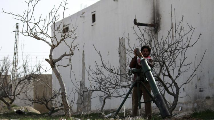 A Free Syrian Army fighter prepares to fire mortar shells in the town of Morek
