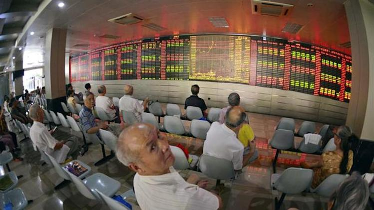 A man looks back at the camera, as investors sit in front of an electronic board showing stock information at a brokerage house in Shanghai August 16, 2013. REUTERS/Stringer/Files