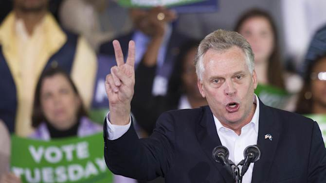 Virginia Democratic gubernatorial candidate Terry McAuliffe flashes a victory sign as he appears at a campaign rallat Washington Lee High School in Arlington, Va., Sunday, Nov. 3, 2013. (AP Photo/Cliff Owen)