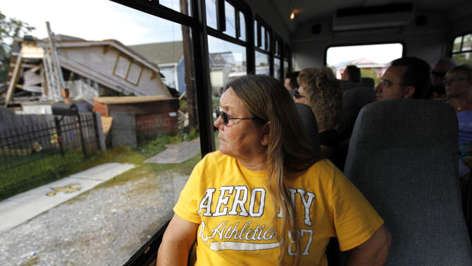 Kathy Stewart, of Enfield, Ill., looks at a blighted home as the tour bus she is riding in passes through the Upper 9th Ward in New Orleans, Tuesday, Oct. 2, 2012. Residents and the City of New Orleans may be pushing back against tour companies ushering out-of-towners into to the Lower 9th Ward, the neighborhood made famous when floodwalls and levees failed in 2005, pushing homes off their foundations and stranding residents on rooftops. (AP Photo/Gerald Herbert)
