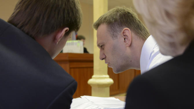 Russian opposition leader Alexei Navalny, centre, reads documents with his lawyers in a courtroom during a trial in Kirov, Russia, Wednesday, April 17, 2013. The trial of the Russian opposition leader accused of embezzling half a million dollars' worth of timber from a state-run company has started in the northwestern city. (AP Photo/Mitya Aleshkovskiy)