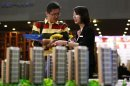 A salesperson talks to a customer behind models of a residential compound at a real estate exhibition in Wuxi