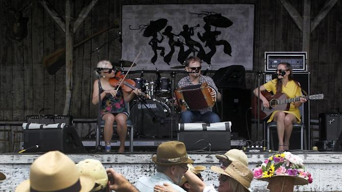 Festival-goers dance to the music of the Cajun band T'Monde, at the Fais Do Do stage during the New Orleans Jazz and Heritage Festival in New Orleans, Friday, April 26, 2013. The band members, from left, are Kelli Jones-Savoy on fiddle, Drew Simon on accordion, and Megan Brown on guitar. (AP Photo/Doug Parker)