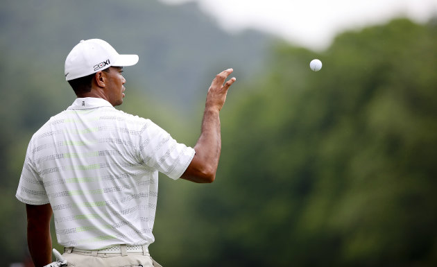 Tiger Woods catches a ball from his caddy during The Greenbrier Classic PGA Golf tournament in White Sulphur Springs, W.Va., Thursday, July 5, 2012. Woods finished the day at 1-over 71.  (AP Photo/The