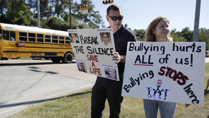 FILE - In this Tuesday, Oct. 5, 2010 file photo, school buses bring students home from Hamilton Middle School in Cypress, Texas, as Brian Carter, left, Sharon Ferranti, foreground right, and others stand on a corner with signs to protest the treatment of Asher Brown, an eighth-grader at the school who killed himself at home on Sept. 23, 2010. His parents blamed his suicide on two years of bullying they say he had suffered at the school. A new Pediatrics study found scientific evidence that it does get better for gay teens, when it comes to bullying, although young gay men fare worse than their lesbian peers. (AP Photo/Houston Chronicle, Karen Warren)  MANDATORY CREDIT