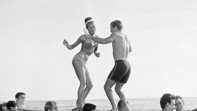 "FILE- In this January 5, 1965, file photo, actors in a Hollywood movie dance ""the twist"" in Malibu, Calif.  The Federal Reserve announced Wednesday, June 20, 2012, it is extending its ""Operation Twist"" program, which is named after the dance craze in an a nod to economic history when the Kennedy administration cut long-term rates while leavings short-term rates alone in the early 1960s.  The program is designed to spur borrowing and spending. (AP Photo/File)"