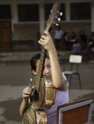 "In this Dec. 11, 2012 photo, Noelia Rios, 12, tunes her guitar made of recycled materials as she practices with ""The Orchestra of Instruments Recycled From Cateura"" in Cateura, a vast landfill outside Paraguay's capital of Asuncion, Paraguay. Children use instruments fashioned out of recycled materials taken from a landfill where their parents eke out livings as trash-pickers, and about 20 of them regularly perform the music of Beethoven and Mozart, Henry Mancini and the Beatles. Noelia's 14-year-old sister and 16-year-old aunt also play in the orchestra. (AP Photo/Jorge Saenz)"