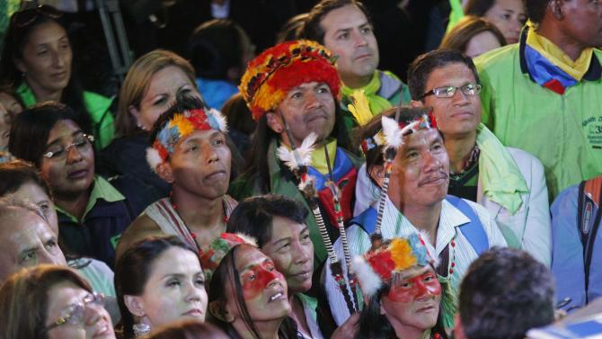 Waorani Indian supporters of Ecuador's President Correa listen as he gives a speech at a political rally in Quito