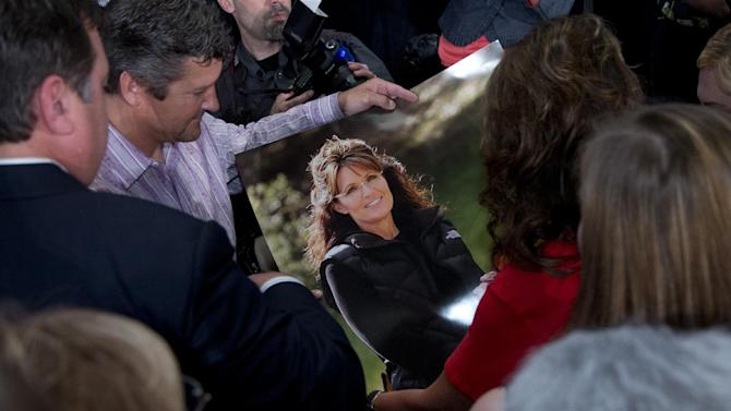 Former Gov. of Alaska Sarah Palin, right in red, signs a poster for a supporter held by her husband Todd Palin, left, during the Faith and Freedom Coalition Road to Majority 2013 conference, Saturday, June 15, 2013, in Washington. Religious conservatives have been skeptical of the RNC's plan for growth, which calls for more tolerant attitudes on immigration and social issues such as abortion and gay marriage, during the three-day gathering of social conservative leaders. Palin, the conference's final speaker, rejected calls for an immigration overhaul that includes a path to citizenship for immigrants in the country illegally. (AP Photo/Carolyn Kaster)