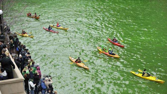 Spectators watch as the Chicago River is dyed green right before the start of the St. Patrick's Day parade in Chicago, Saturday, March, 16, 2013.  With the holiday itself falling on a Sunday, many celebrations were scheduled instead for Saturday because of religious observances. (AP Photo/Paul Beaty)