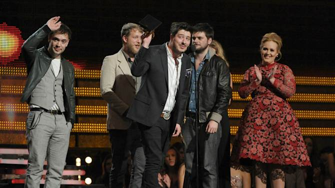 "Mumford & Sons, from left, Ben Lovett, Ted Dwayne, Marcus Mumford and Country Winston Marshall accept the award for album of the year for ""Babel"" at the 55th annual Grammy Awards on Sunday, Feb. 10, 2013, in Los Angeles. Looking on from right is presenter Adele. (Photo by John Shearer/Invision/AP)"