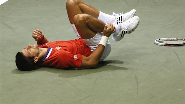 Novak Djokovic holds his ankle (Reuters)