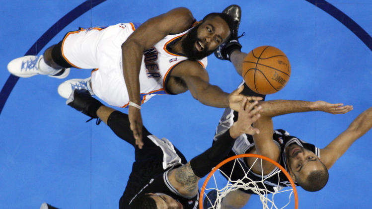 Oklahoma City Thunder guard James Harden, toip, shoots against San Antonio Spurs guard Danny Green, bottom, left, and guard Tony Parker, of France, during the first half of Game 4 in the NBA basketball playoffs Western Conference finals, Saturday, June 2, 2012, in Oklahoma City. (AP Photo/Sue Ogrocki)