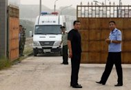 Chinese police wait outside the Number Two prison after the release of dissident Wang Xiaoning in Beijing