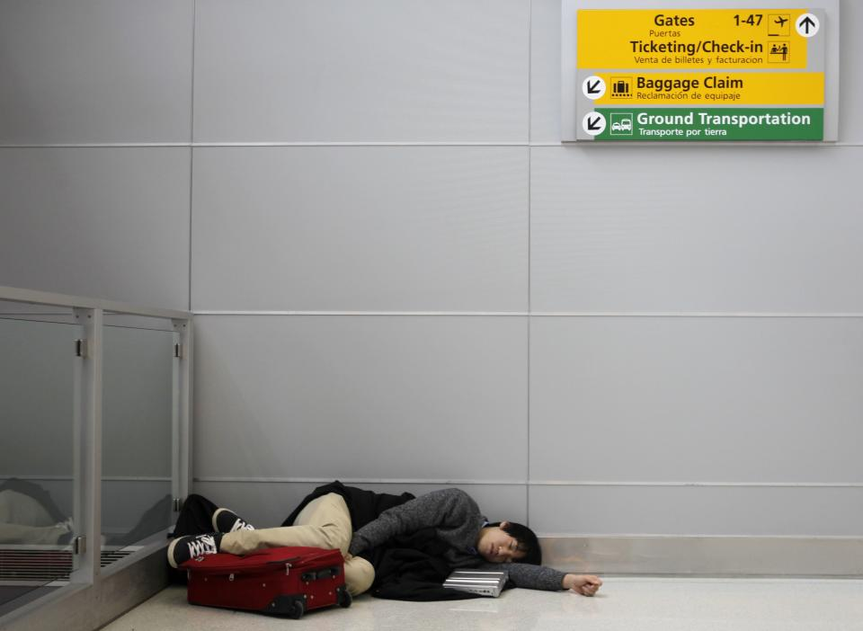 An airline passenger sleeps on the floor of a terminal at John F. Kennedy International Airport in New York, Monday, Dec. 27, 2010.  (AP Photo/Seth Wenig)