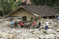Residents walk next to a house damaged by a landslide in Campo Grande neighborhood, Teresopolis, Rio de Janeiro state, Brazil, Saturday Jan. 15, 2011. After four nights of torrential rains, mud and landslides have killed more than 500 people in the Rio de Janeiro area.