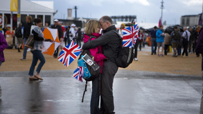 A couple embrace at the Olympic Park during the 2012 Summer Olympics, Sunday, July 29, 2012, in London. (AP Photo/Emilio Morenatti)
