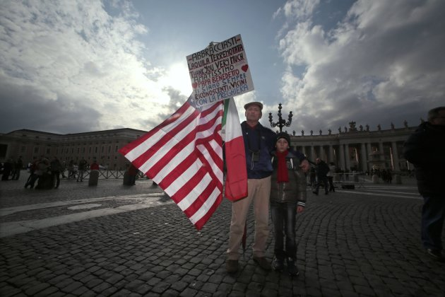 A pilgrim and his son hold a sign as they wait to attend Pope Benedict XVI's last Angelus in Saint Peter's Square at the Vatican