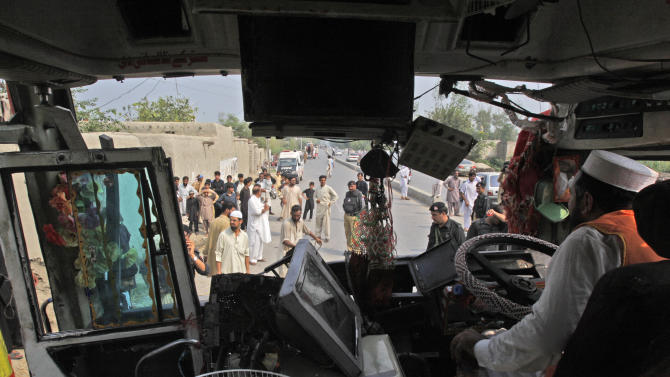 A Pakistani rescue worker inspects the wreckage of a bus which was destroyed in a bomb blast, in Peshawar, Pakistan, Friday, Sept. 27, 2013. The bomb exploded in the back of a bus carrying government employees in northern Pakistan on Friday, killing and wounding dozens of people, officials said. (AP Photo/Mohammad Sajjad)
