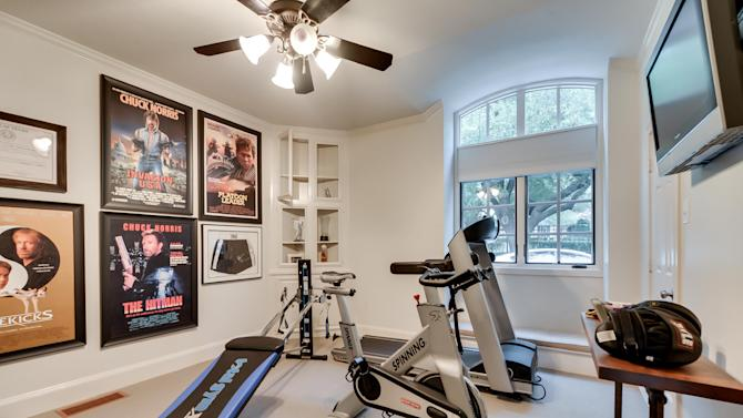 """This July 15, 2013 photo courtesy of Rogers Healy and Associates Real Estate shows the gym in Texas Ranger Cordell Walker's house from the former television series """"Walker, Texas Ranger,"""" in Dallas. Rogers Healy, of Rogers Healy and Associates Real Estate has listed the 7,362-square-foot home for $1.2 million. The seven-bathroom and four-bedroom has been extensively renovated since the show ended in 2001. (AP Photo/Rogers Healy and Associates Real Estate)"""