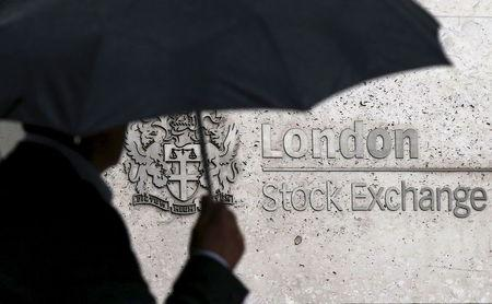 File photo of a man sheltering under an umbrella as he walks past the London Stock Exchange