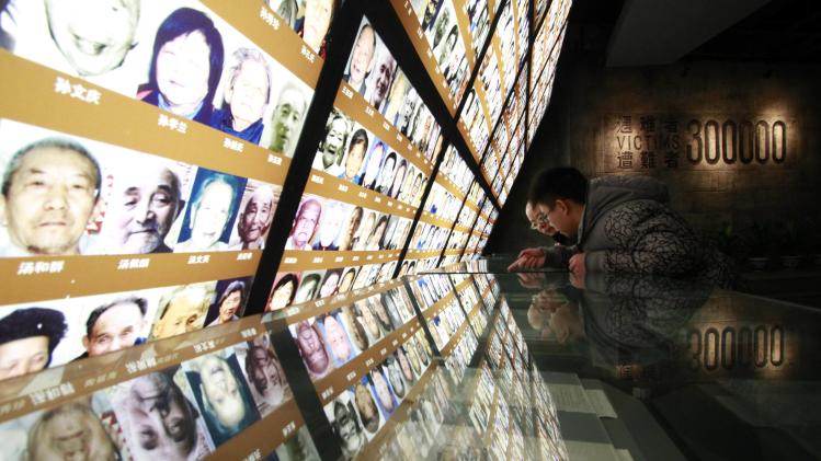 Visitors lean on an exhibition stand ahead of 76th anniversary of the start of the Nanjing Massacre at the Nanjing Massacre Museum