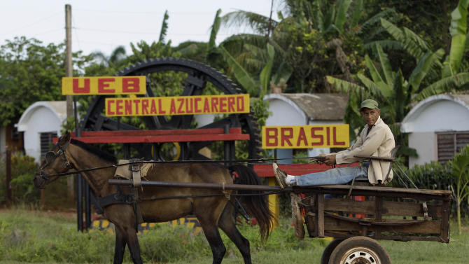 """In this Sept. 8, 2012 photo, a man rides in a horse-drawn carriage outside the sugar processing plant """"Brasil"""" in Jaronu, Cuba.  Just two years ago, Cuba's sugar industry was on its knees after the worst harvest in more than a century. Now Cuba's signature industry is showing signs of life. Hulking processing plants are coming back online, and the harvest is growing by double digits each year, a boon to rural towns like Jaronu. (AP Photo/Franklin Reyes)"""