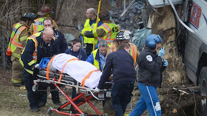 Emergency rescue crews remove a victim of a tour bus crash on the Pennsylvania Turnpike on Saturday, March 16, 2013 near Carlisle, Pa.  Authorities say the tour bus crashed on the freeway at mile marker 227 in central Pennsylvania, and serious injuries have been reported.  Lacrosse players from Seton Hill University and three coaches were among the 23 people aboard when the bus crashed at about 9 a.m., turnpike spokeswoman Renee Colborn said. It's not clear what caused the crash, but state police were investigating, said Megan Silverstram of the Cumberland County public safety department. (AP Photo/The Sentinel, Jason Malmont ) MANDATORY CREDIT