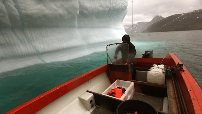 FILE - In this July 26, 2011 file photo, a Greenlandic Inuit hunter and fisherman steers his boat past a melting iceberg, along a fjord leading away from the edge of the Greenland ice sheet, near Nuuk, Greenland. Nearly 4 out of 5 Americans now think temperatures are rising and that global warming will be a serious problem for the United States if nothing is done about it, a new Associated Press-GfK poll finds. Belief and worry about climate change are inching up among Americans in general, but concern is growing faster among people who don't often trust scientists on the environment. In follow-up interviews, some of those doubters said they believe their own eyes as they've watched thermometers rise, New York City subway tunnels flood, polar ice melt and Midwestern farm fields dry up. (AP Photo/Brennan Linsley, File)