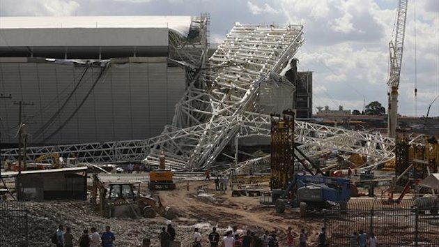 Workers stand near a crane that collapsed on the site of the Arena Sao Paulo stadium. (Reuters)