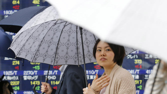 People under umbrellas walk by an electronic stock board of a securities firm in Tokyo, Monday, May 20, 2013. Japan's Nikkei 225 index jumped 1.4 percent to 15,352.84 as evidence of a steady economic recovery in the U.S. helped push Asian stock markets higher Monday. (AP Photo/Koji Sasahara)