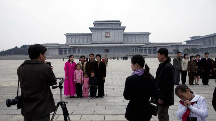 In this April 15, 2011 photo, families have their photographs taken in front of the Kumsusan Memorial Palace in Pyongyang, North Korea. The palace, which was the official residence of Kim Il Sung until his death in 1994, is now a mausoleum where his embalmed body lies in state. (AP Photo/David Guttenfelder)