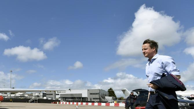 Britain's Prime Minister David Cameron walks to board an aircraft to travel to an election rally from Luton Airport