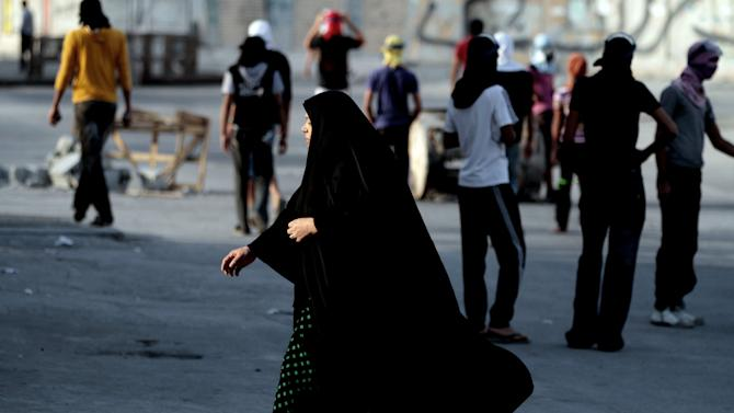 A Bahraini woman walks past Bahraini anti-government protesters during clashes with riot police in Ma'ameer, Bahrain, Thursday, Jan. 24, 2013. Riot police in Bahrain fired tear gas and stun grenades at anti-government protesters whose chants included calls to reject proposed talks aimed at easing nearly two years of unrest in the Gulf nation. (AP Photo/Hasan Jamali)