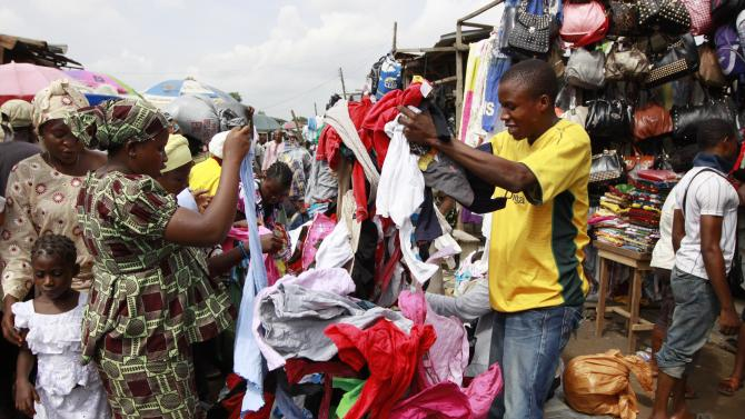 In this photo taken Monday, June. 18, 2012. People buy secondhand clothes at Katangua market in Lagos, Nigeria. Shipping container after shipping container arrives to this market in Lagos, Nigeria's largest city, filled to the brim with plastic-wrapped bales of secondhand clothes from the U.S. and elsewhere in the world. Traders scour, barter, hem and haw over T-shirts, bras, pants and shoes sent to help clothe a nation of more than 160 million people where the textile industry largely collapsed years ago.  (AP Photo/Sunday Alamba)