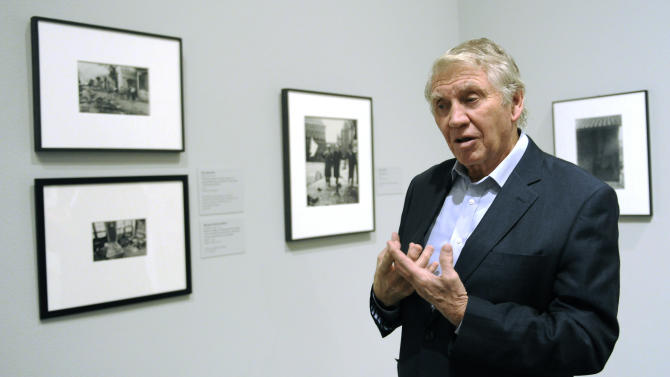 In this Thursday, Nov. 8, 2012 photo, photographer Don McCullin discusses his feelings and work as a war photographer while being interviewed at the Houston Museum of Fine Arts' war photography exhibit in Houston. The exhibit includes the work of 280 photographers from 28 nations covering the Mexican-American war in 1846 to present-day. McCullin has four photos in the exhibit. (AP Photo/Pat Sullivan)