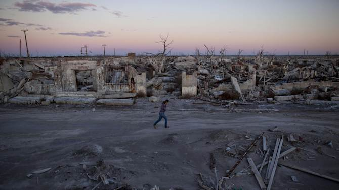 In this May 6, 2013 photo, former resident and tourist guide Norma Berg walks by a street in Epecuen, a village that once was submerged in water in Argentina. People come to see the rusted hulks of automobiles and furniture, crumbled homes and broken appliances. They climb staircases that lead nowhere, and wander through a graveyard where the water toppled headstones and exposed tombs to the elements.   (AP Photo/Natacha Pisarenko)