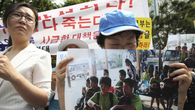 An unidentified North Korean defector holds a picture of nine North Korean defectors who were flown home as she cries during a rally protesting against Laos' repatriation of them, in front of Foreign Ministry in Seoul, South Korea, Wednesday, June 5, 2013. The defectors, seven male and two female, were flown home from China last week. They had been captured in Laos some 17 days earlier, along with a South Korean missionary who tried to help them take asylum at a foreign embassy in the Southeast Asian country, according to South Korean officials and activists. Before they were captured in Laos and sent home, the young group of North Korean defectors smiled and teased each other as they told an activist how some of them were beaten with sticks for trying to steal noodles in their homeland. (AP Photo/Ahn Young-joon)