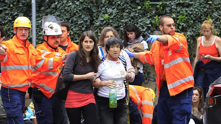 Paramedics help injured people after an explosion in downtown Prague, Czech Republic, Monday, April 29, 2013.  Police said a powerful explosion has damaged a building in the center of the Czech capital and they believe some people are buried in the rubble. (AP Photo/Petr David Josek)
