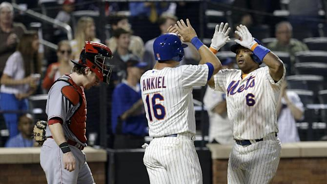 New York Mets' Marlon Byrd, right, is greeted by Rick Ankiel, center, while Cincinnati Reds catcher Ryan Hanigan watches after Byrd hit a three-run home run during the third inning of the baseball game at Citi Field Monday, May 20, 2013 in New York. (AP Photo/Seth Wenig)