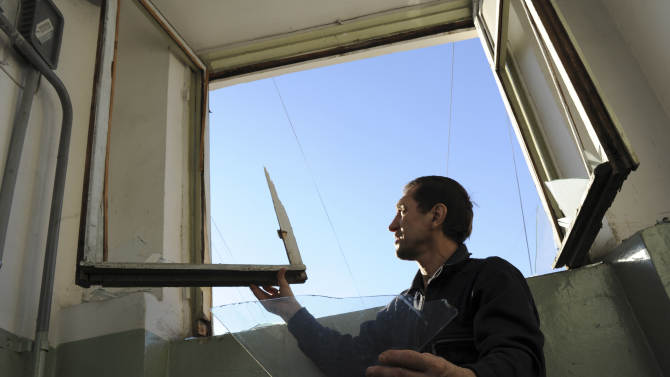 A local resident repairs a window broken by a shock wave from a meteor explosion in Chelyabinsk, about 1500 kilometers (930 miles) east of Moscow,  Friday, Feb. 15, 2013. A meteor that scientists estimate weighed 10 tons (11 tons) streaked at supersonic speed over Russia's Ural Mountains on Friday, setting off blasts that injured some 500 people and frightened countless more. (AP Photo/Boris Kaulin)
