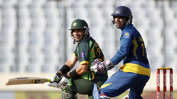 Pakistan's captain Misbah-ul-Haq plays a ball as Sri Lanka's wicketkeeper Kumar Sangakkara watches during their 2014 Asia Cup final match in Dhaka