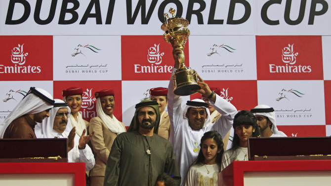 In this Saturday, March 31, 2012 file photo, with Sheikh Mohammed bin Rashid Al Maktoum, prime minister and ruler of Dubai on his left, Mahmoud al-Zarooni, the trainer of Monterosso from Great Britain holds the trophy after they won the Dubai World Cup race in Dubai, United Arab Emirates. Zarooni was charged with violating multiple rules related to banned substances in horses after samples from 11 of his horses at stables in Newmarket including 1000 Guineas favorite Certify were found to contain traces of anabolic steroids. (AP Photo/Kamran Jebreili, File)