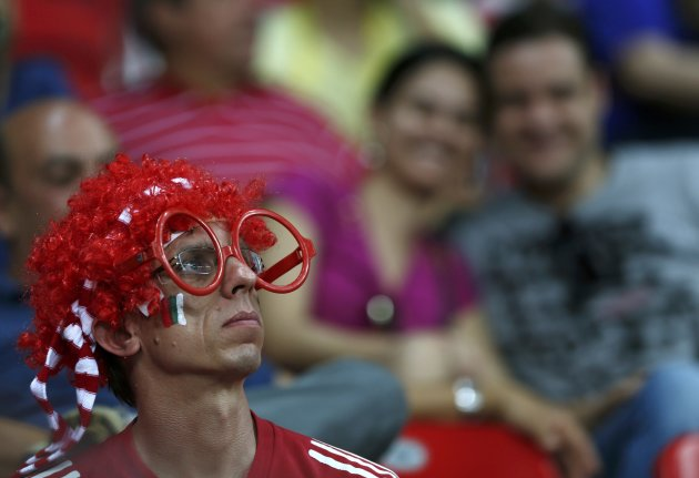 A fan of Italy wearing a wig and party glasses waits before the team's Confederations Cup Group A soccer match against Japan at the Arena Pernambuco in Recife
