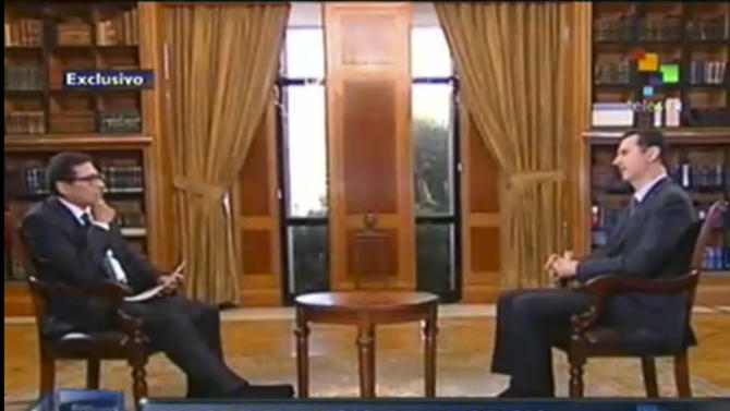 "In this frame grab taken from online video broadcast on Telesur television on Wednesday, Sept. 25, 2013, Syria's President Bashar Assad, right, speaks during an interview with Telesur reporter William Parra in Damascus, Syria. The quote attributed to Assad reads in Spanish ""From the beginning of the crisis the United States based themselves on lies."" (AP Photo/Telesur)"