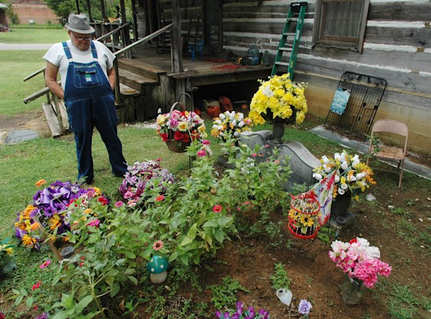 In this Friday, Aug. 10, 2012 photo, James Davis, 73, stands over the grave of his wife, Patsy, in the front yard of the home they shared in Stevenson, Ala. The city sued to make Davis move his wife&#39;s remains from the residential tract, and Davis is asking the Alabama Court of Civil Appeals to block an order requiring him to disinter her remains. (AP Photo/Jay Reeves)
