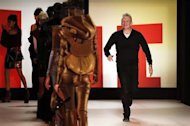 French designer Jean Paul Gaultier appears with models at the end of his Fall-Winter 2013/2014 women's ready-to-wear fashion show during Paris fashion week March 2, 2013. REUTERS/Benoit Tessier