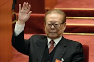 Former Chinese president Jiang Zemin raises his hands to vote for a report at the closing of the 18th Communist Party Congress at the Great Hall of the People in Beijing on 14 November 2012. Former Chinese leader Jiang Zemin has requested a lower rank in the Communist Party protocol, according to state media, with experts saying Thursday he bowed to pressure from outgoing President Hu Jintao